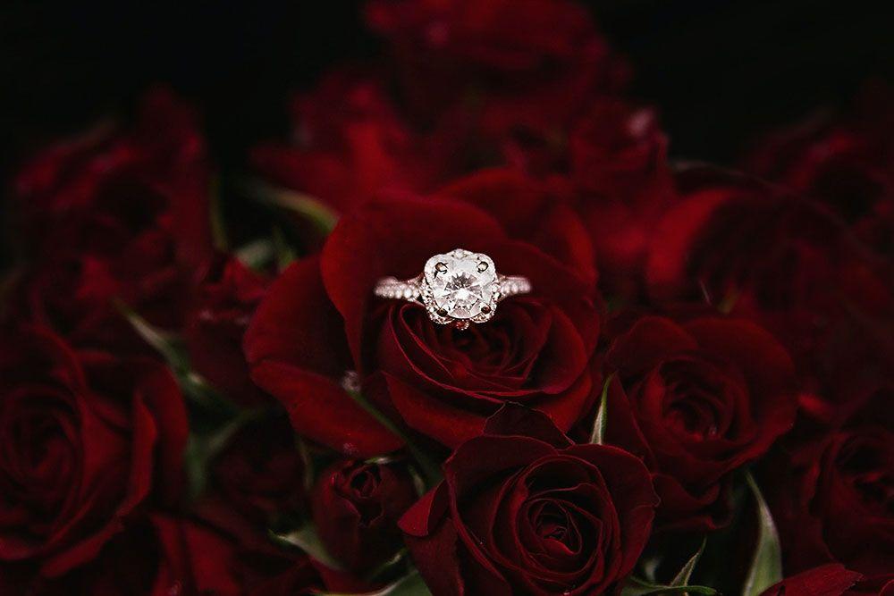 timanttisormus punaisten ruusujen päällä